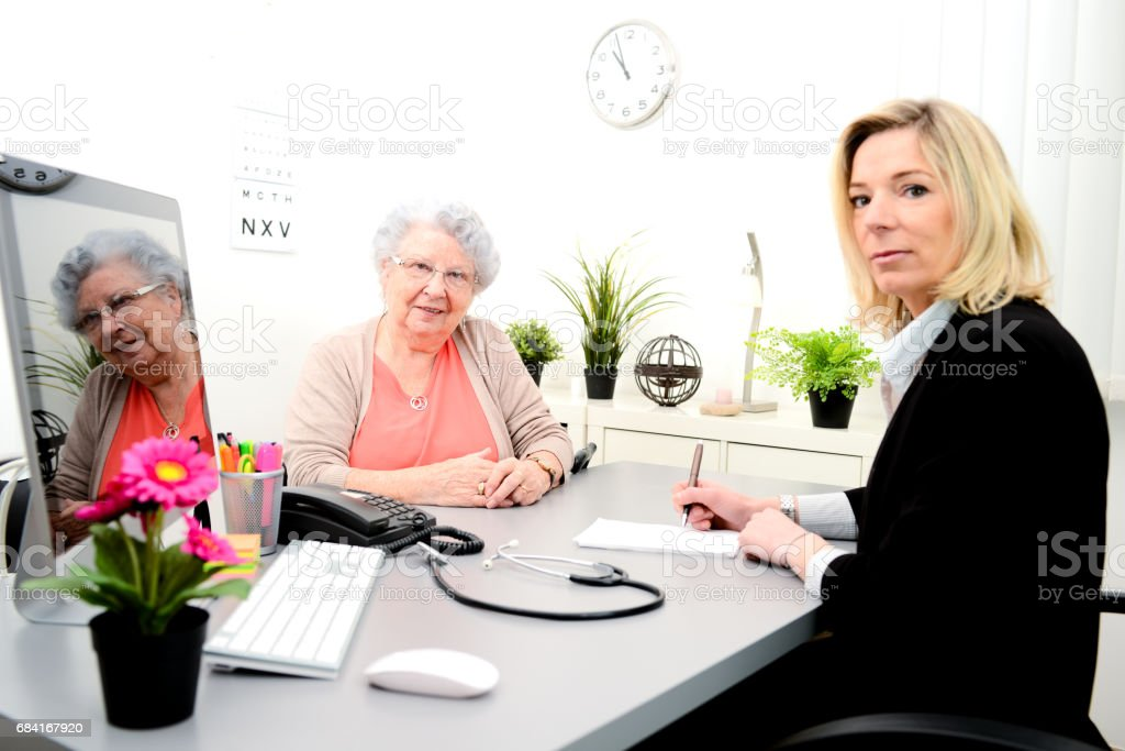 Mature female doctor in her office writing a medicine prescription to an elderly senior woman foto stock royalty-free