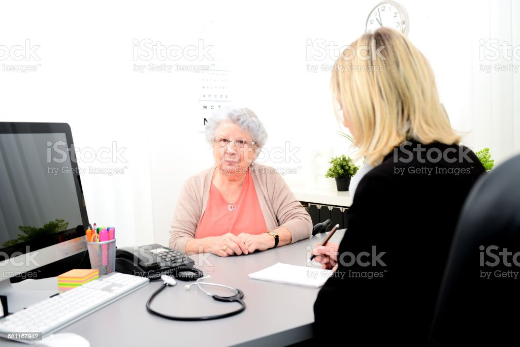 Mature female doctor in her office writing a medicine prescription to an elderly senior woman photo libre de droits