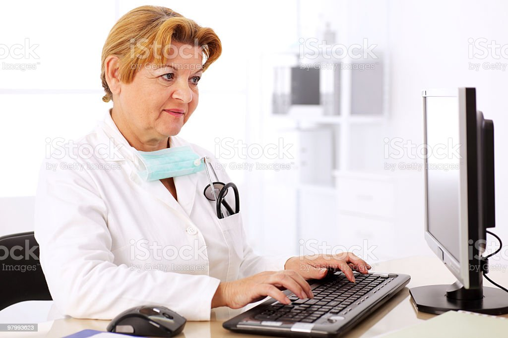 Mature female doctor typing on computer keyboard. royalty-free stock photo