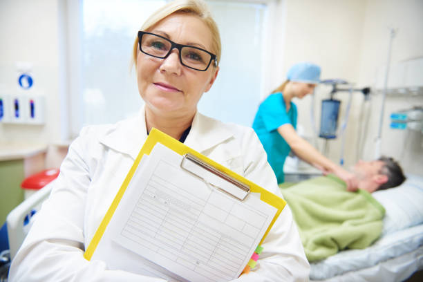 Mature female doctor with medical record stock photo
