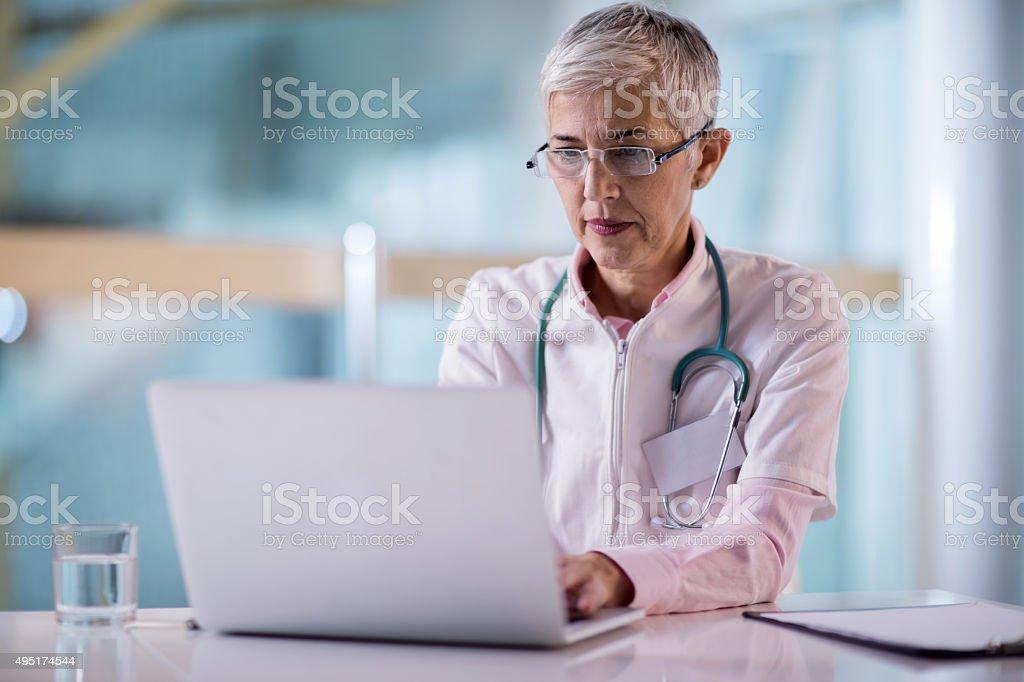 Reife Ärztin Arbeiten am laptop im Büro. – Foto