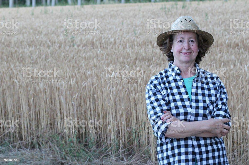 Mature female farmer smiling on farmland - Photo