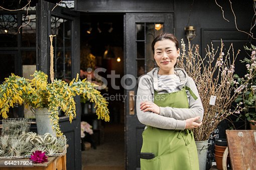istock Mature female florist standing at the entrance of her flower shop. 644217924