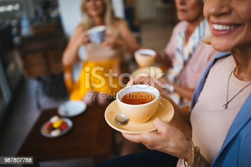 Close-up of senior women relaxing and drinking tea together at coffee shop in the afternoon