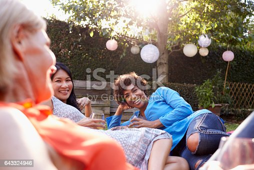 istock Mature Female Friends Enjoying Drinks In Backyard Together 643324946