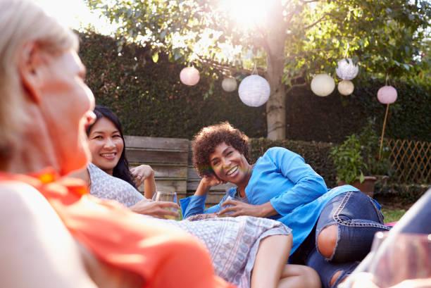 reifen sie freundinnen genießen drinks im hinterhof zusammen - mensch isst gras stock-fotos und bilder