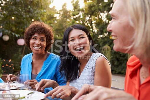 istock Mature Female Friends Enjoying Outdoor Meal In Backyard 643324648