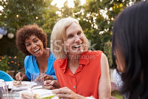 istock Mature Female Friends Enjoying Outdoor Meal In Backyard 643324814