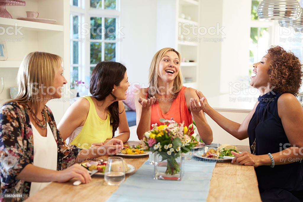 Mature Female Friends Sitting Around Table At Dinner Party stock photo