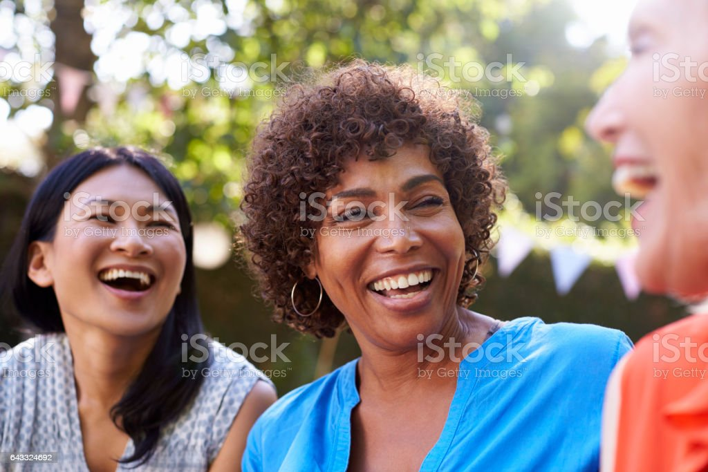 Mature Female Friends Socializing In Backyard Together stock photo