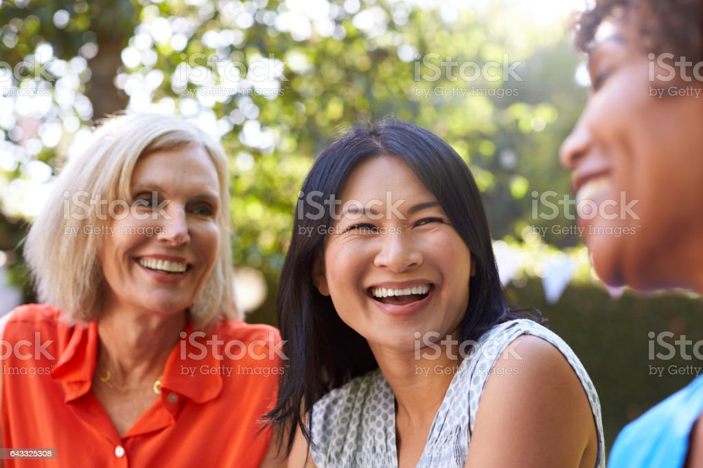 Mature Female Friends Socializing In Backyard Together royalty-free stock photo