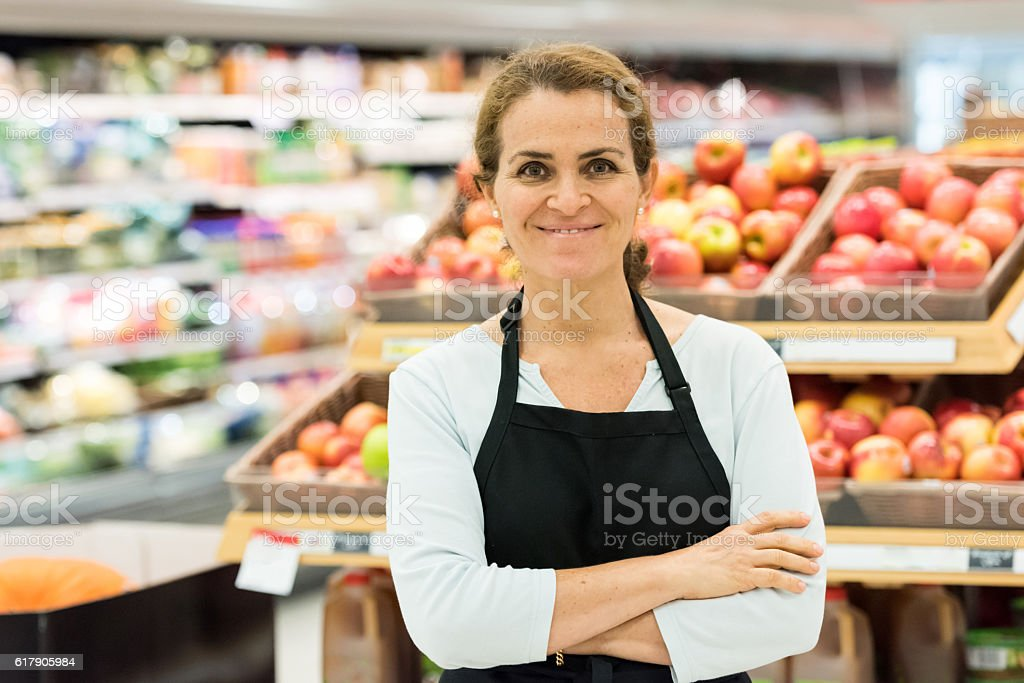 Mature female grocery store worker stock photo