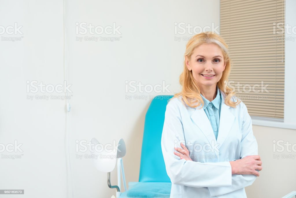 mature female gynecologist with crossed arms in front of gynecology