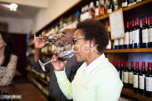 Senior woman drinking red wine in tasting room with people sitting by. Mature female tasting wine in a winery.