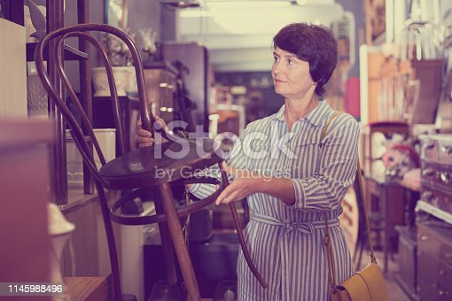 Mature female is choosing old armchair for home in antique shop.