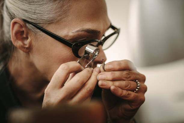 Mature female jeweler looking at stone through loupe Mature female jeweler looking at stone through loupe to inspect it. Close up of senior jewelry maker looking at the gem while working at workshop. jeweller stock pictures, royalty-free photos & images
