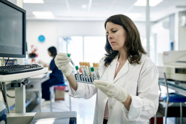 Mature Female Pathologist Examining Test Tube Samples in Lab Close-up of serious Hispanic female pathologist in white coat examining test tube rack samples in Buenos Aires clinical analysis laboratory. immunology stock pictures, royalty-free photos & images