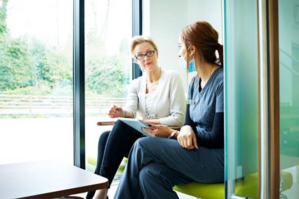 mogen kvinnlig patient prata med sjuksköterska i väntrum - two dentists talking bildbanksfoton och bilder