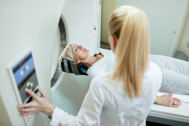 Mature female patient undergoing for CT scan examination in the hospital. High angle view of mature woman and radiologist during MRI scan examination at clinic. mri scan stock pictures, royalty-free photos & images