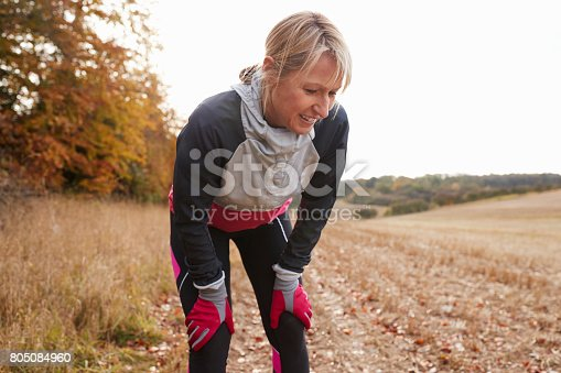 istock Mature Female Runner Pausing For Breath During Exercise In Woods 805084960
