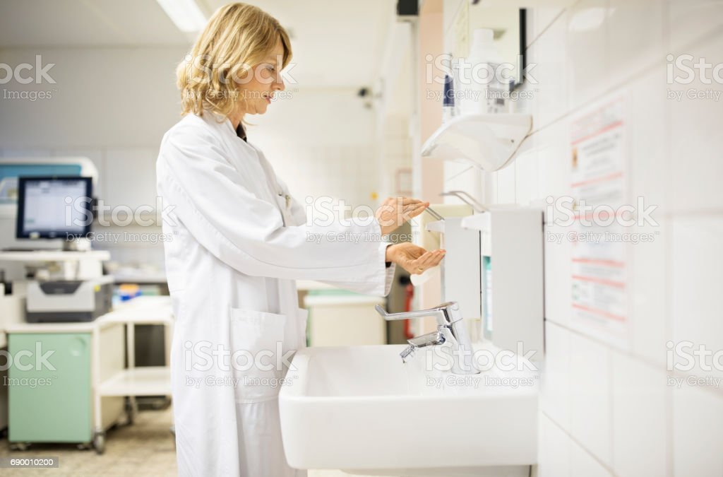 Mature female scientist dispensing soap by sink stock photo