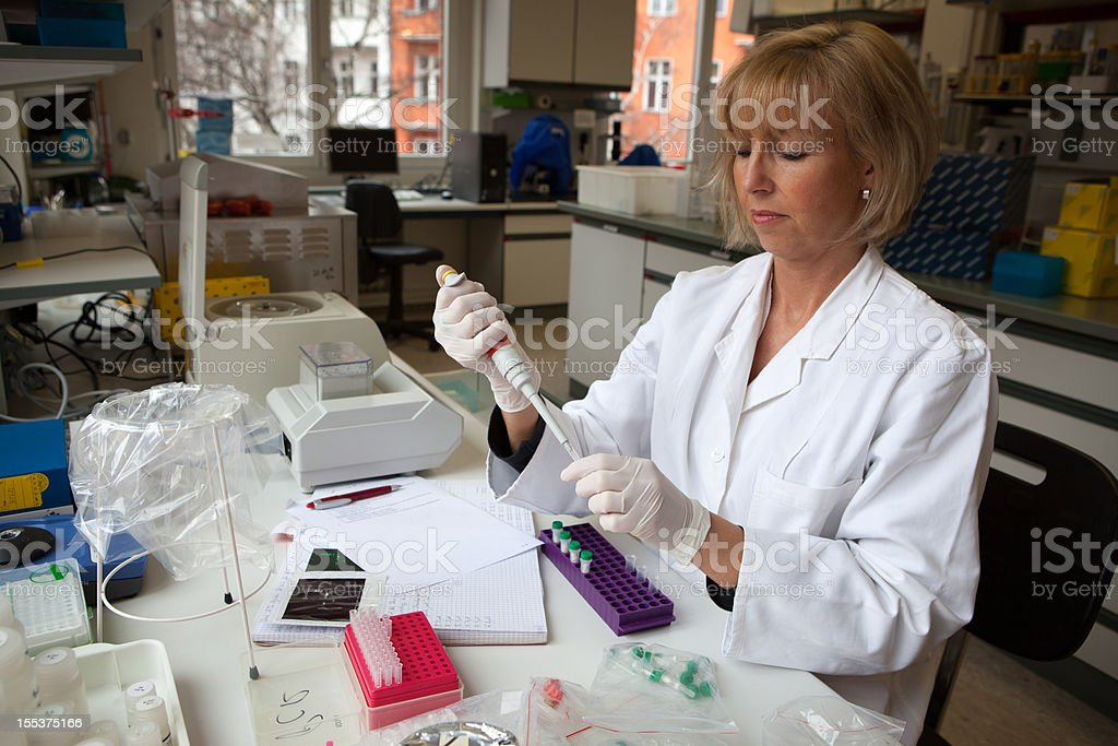 mature female Scientist works with  pipette at scientific Experiment royalty-free stock photo