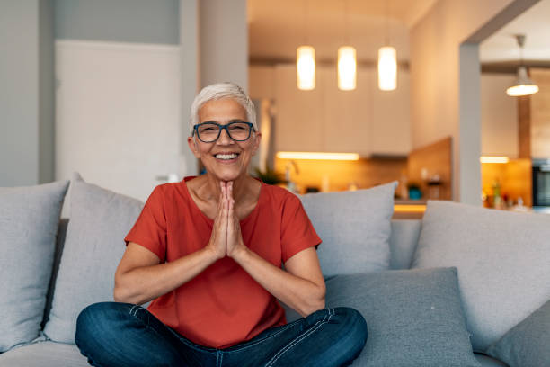 Mature female sitting in lotus position doing yoga at home Photo of of a senior female doing yoga in her living room. Thoughtful mature woman dreaming about something, dreamy aged female enjoying free time at home, thinking about pleasant memories, reminiscent elderly lady leisure morning. Happy lazy senior old woman relaxing meditating leaning on comfortable sofa at home, calm mindful middle aged lady resting breathing fresh air having nap with eyes open feel no stress free relief. relief emotion stock pictures, royalty-free photos & images