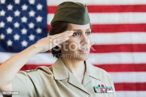Serious mature Hispanic female military officer salutes the American flag.