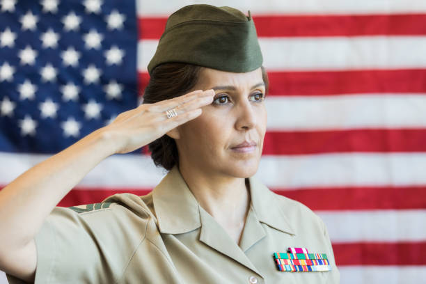 Mature female soldier salutes American flag Serious mature Hispanic female military officer salutes the American flag. officer military rank stock pictures, royalty-free photos & images
