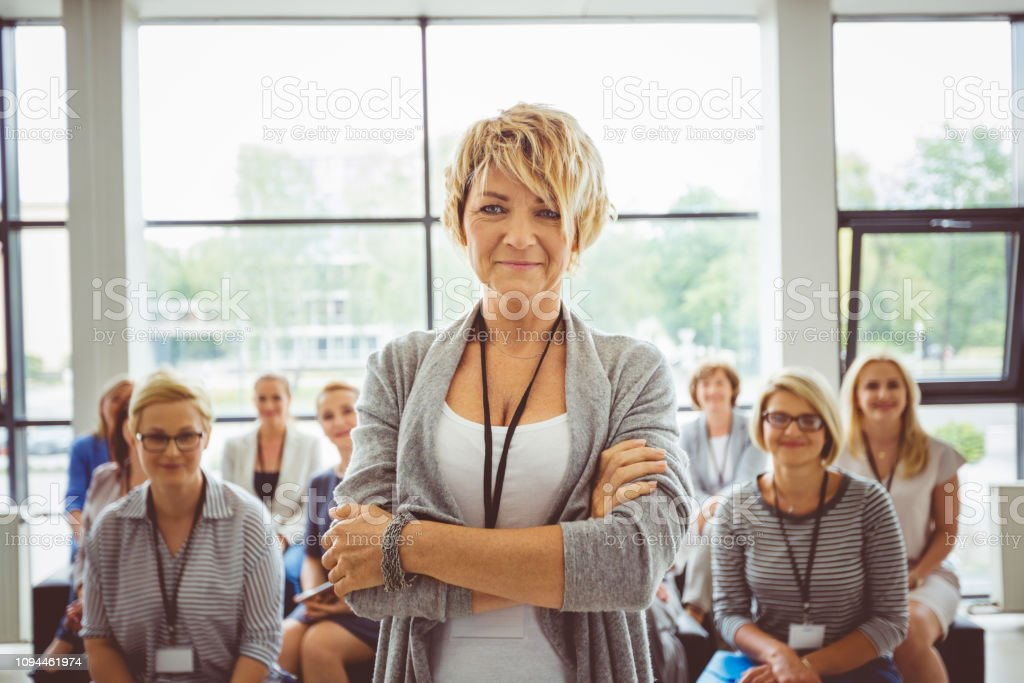 Mature female speaker with audience at back Happy mature woman speaker standing with her arms crossed in seminar hall with her audience sitting in background Adult Stock Photo