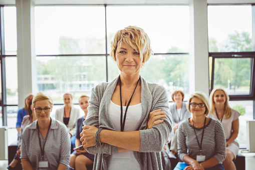 Mature Female Speaker With Audience At Back Stock Photo - Download Image Now