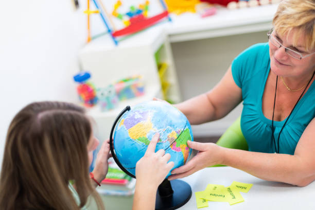 Mature female therapist working with a teenage girl with learning difficulties. Private geography tutoring session. Teacher with teenage student in class pointing to countries on a globe. stock photo