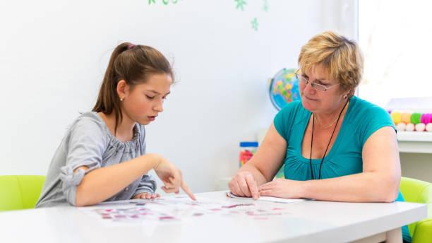 Reifen weiblichen Therapeuten arbeiten mit ein junges Mädchen mit Lernschwierigkeiten zu Meister logische Tests. – Foto