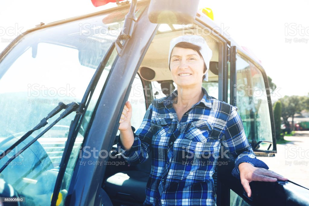 Mature female worker in tractor on farm stock photo