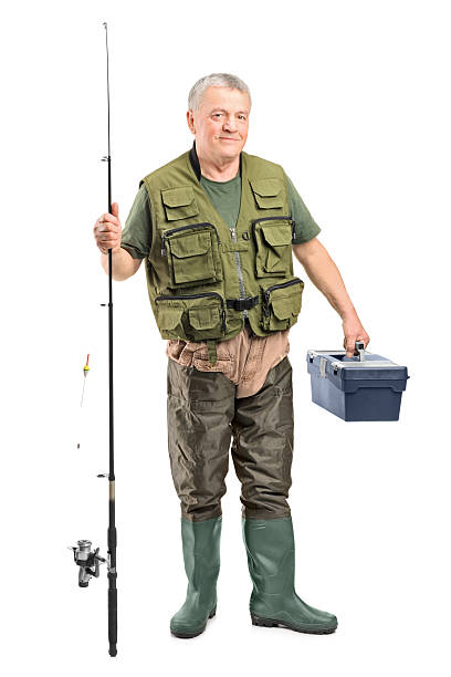 Mature fisherman holding a fishing equipment Full length portrait of a mature fisherman holding a fishing equipment isolated on white background fisherman stock pictures, royalty-free photos & images