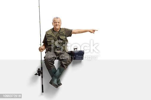 Full length portrait of a mature fisherman with a fishing rod sitting on a panel and pointing isolated on white background