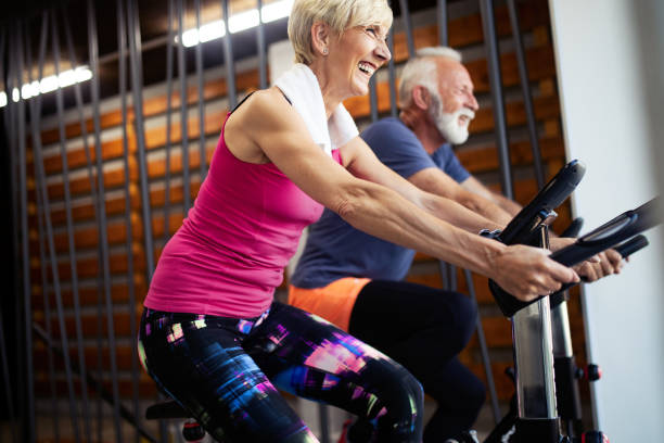 Mature fit people biking in the gym, exercising legs doing cardio workout cycling bikes Fit senior people biking in the gym, exercising legs doing cardio workout cycling bikes cardiovascular exercise stock pictures, royalty-free photos & images