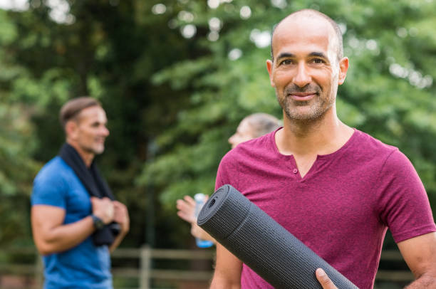 Mature fitness man Smiling mature man holding yoga mat and looking at camera. Portrait of a happy mixed race man with yoga mat at park after fitness exercise. Healthy positive senior man holding yoga mat with people in background. yoga instructor stock pictures, royalty-free photos & images