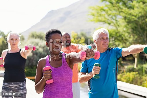 Happy senior and mature couples exercising with dumbbells. Healthy multiethnic people exercising using dumbbells outdoor. African couple and senior friends in sportswear stretching arms holding colorful dumbbells at park.