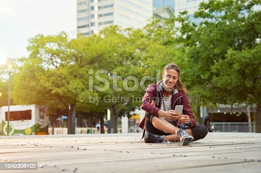 Fitness runner on mobile smart phone app tracking progress. Athlete mature woman in sportswear listening music with earphones on city street. Latin sporty woman sitting on floor and using smartphone with copy space.