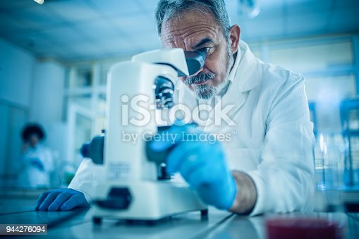 Concentrated male scientist analyzing something through a microscope.