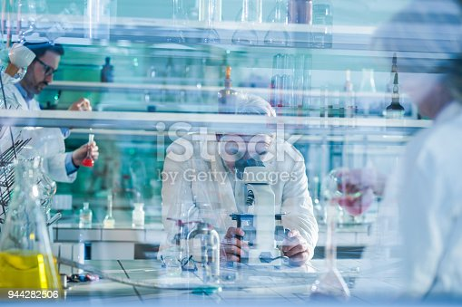 499203366 istock photo Mature forensic scientist using microscope while working with his colleagues in laboratory. 944282506