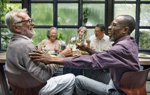 Mature friends at a dinner party stock photo