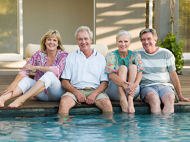 Mature friends by swimming pool stock photo
