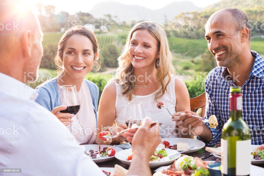 Mature friends enjoying eating - foto stock