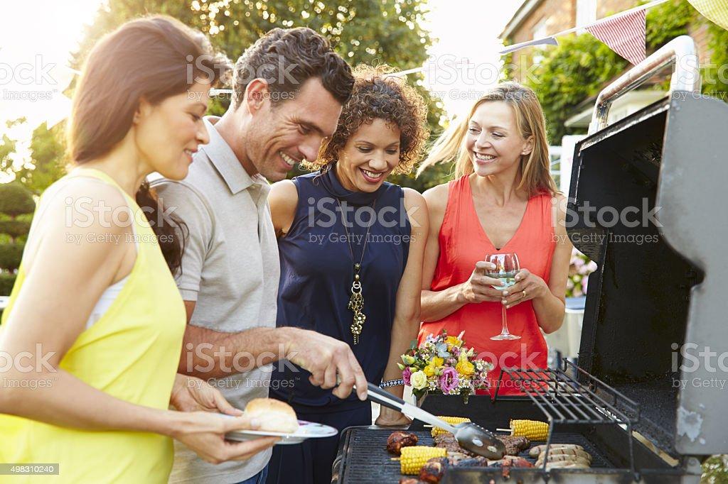 Mature Friends Enjoying Outdoor Summer Barbeque In Garden foto
