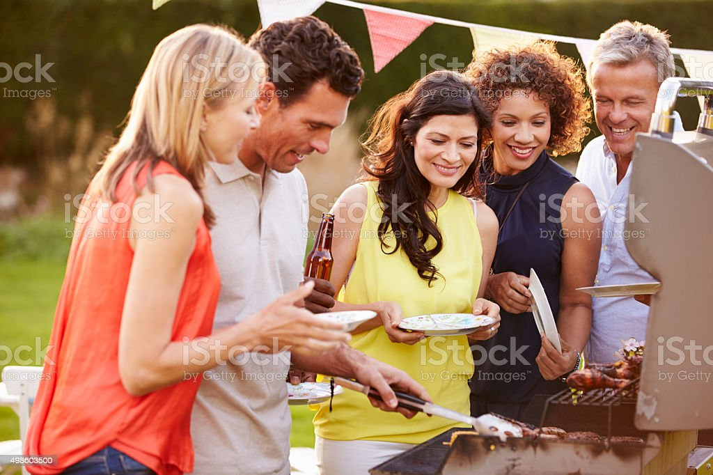 Mature Friends Enjoying Outdoor Summer Barbeque In Garden​​​ foto