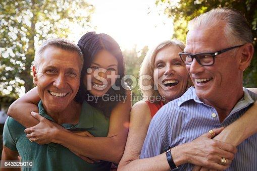 istock Mature Friends Giving Piggybacks In Backyard Together 643325010