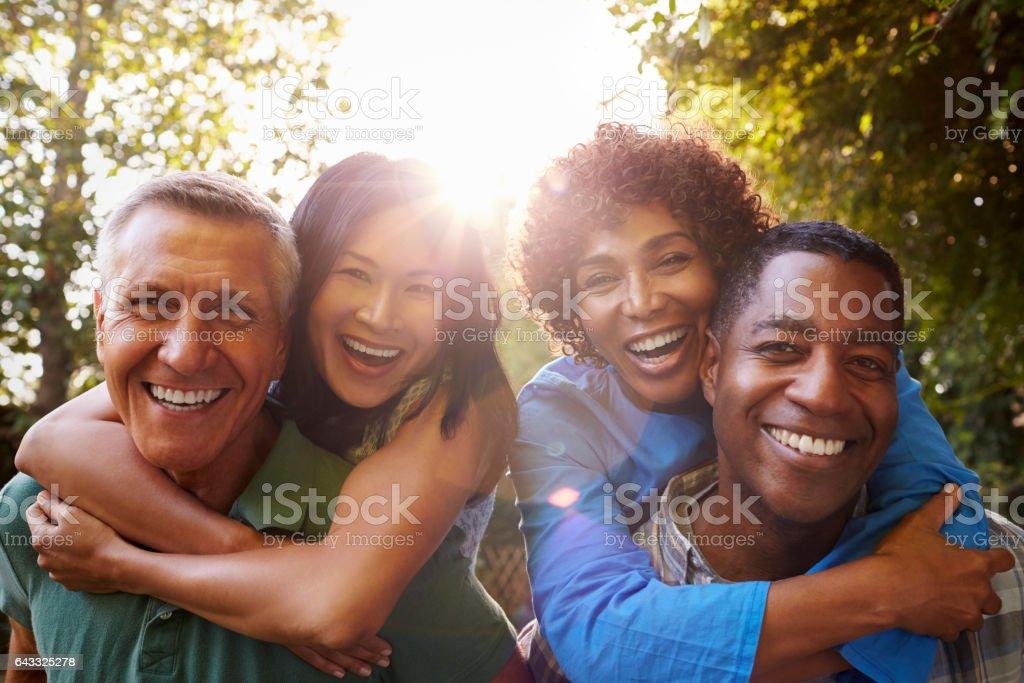 Ältere Freunde zusammen Hinterhof Piggybacks nachgebend - Lizenzfrei Erwachsener über 40 Stock-Foto