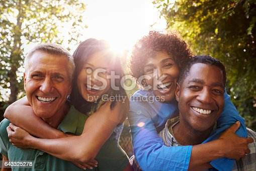 istock Mature Friends Giving Piggybacks In Backyard Together 643325278